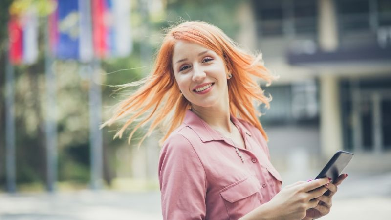 red haired woman smiling happily at the camear