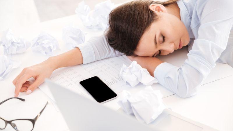 sleep deprived woman asleep on desk with phone beside her