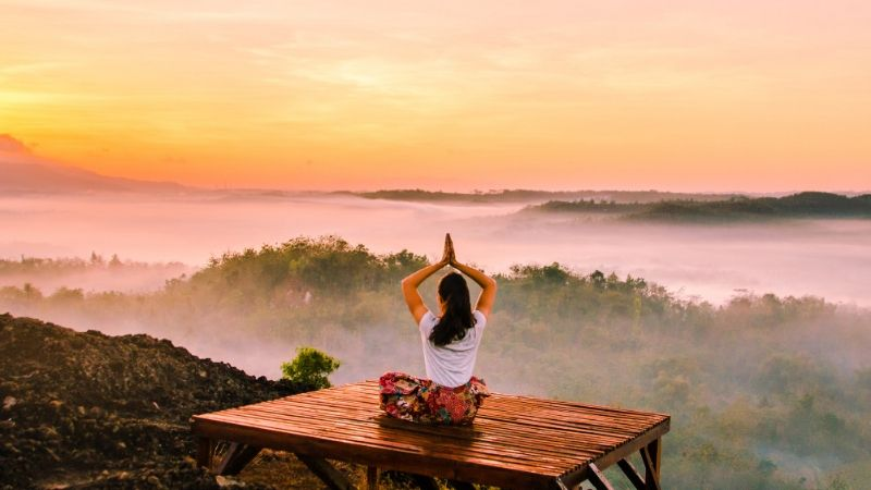 woman doing a yoga pose on a table overlooking a valley