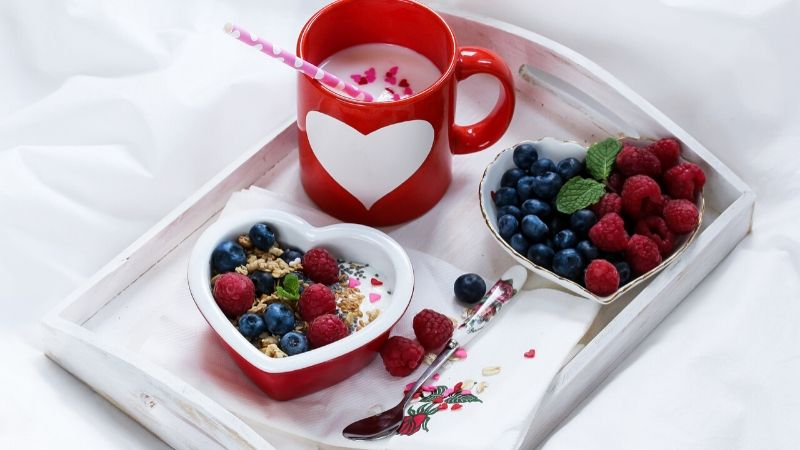 valentine's special breakfast in bed with two heart-shaped bowls filled with berries, one red mug with a white heart on it and hot chocolate inside