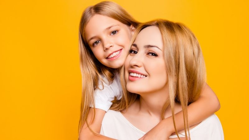 blonde woman and child against a bright yellow background